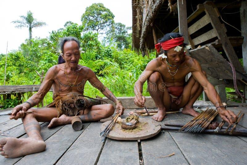 Den manMentawai stammen förbereder pilar för att jaga arkivfoton