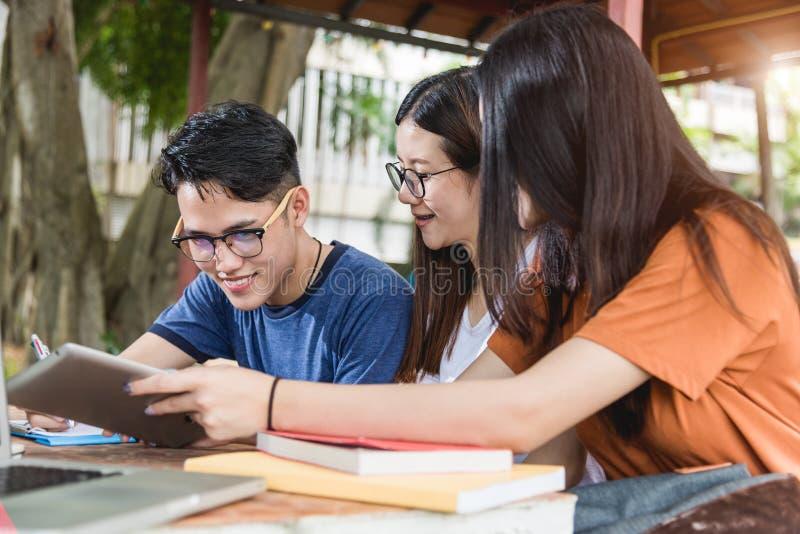Den manstudenter och flickv?nnen ?r konsulterar information fr?n den utomhus- datorb?rbara datorn, minnestavlan och boken fotografering för bildbyråer