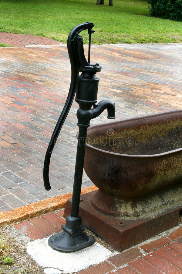 Den manuella vattenpumpen och badar arkivbild