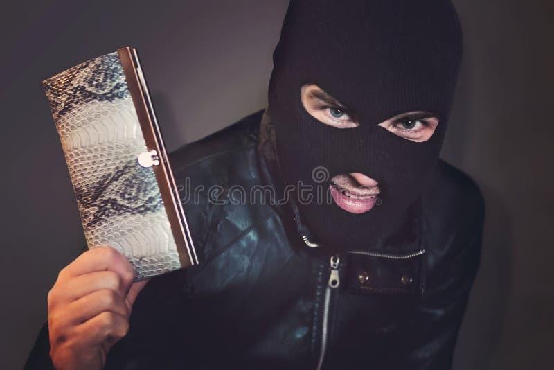 Den maskerade brottslingen på den svarta bakgrunden grinar se tittaren och visa en handväska i hand Ondska-göraren är glad till arkivfoto