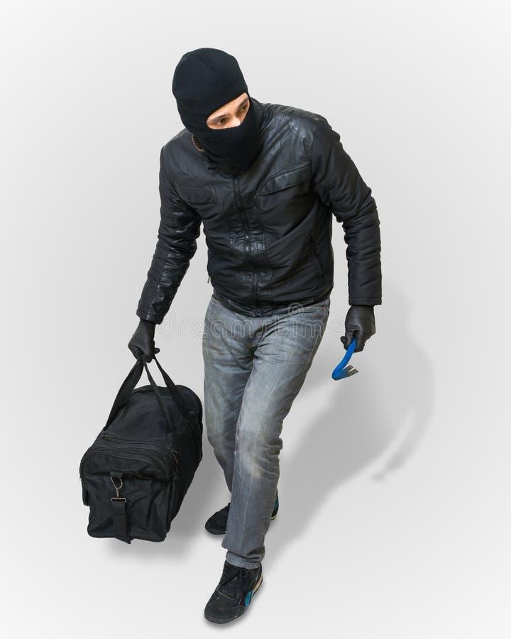 Den maskerade inbrottstjuven eller tjuven med balaclavaen kryper med svarta lodisar royaltyfri fotografi