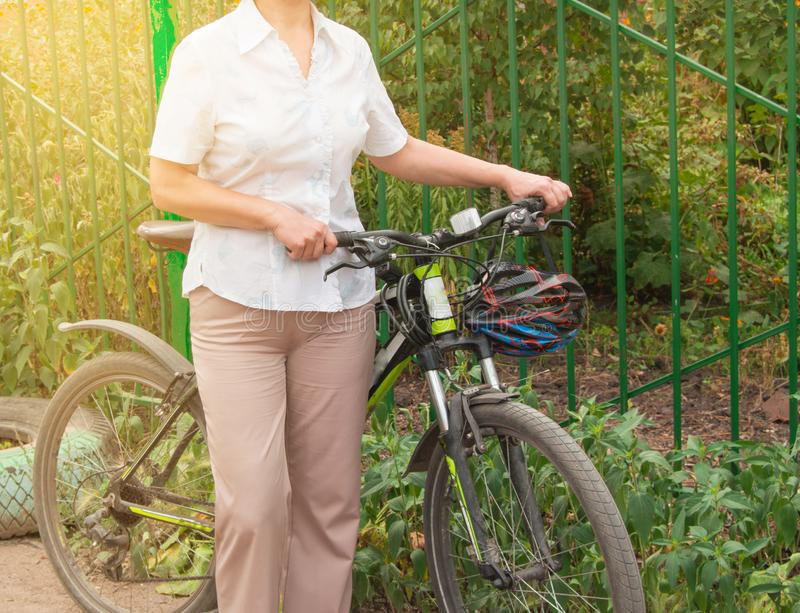 Den medel?ldersa attraktiva slanka kvinnan i ljus byxa och skjortast?llningar n?ra cykeln i parkerar p? en solig sommardag som cy arkivfoto