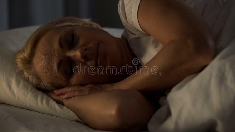 Den medelåldersa kvinnan som ler att sova i säng, lugna känsla och salighet, natt vilar royaltyfri bild