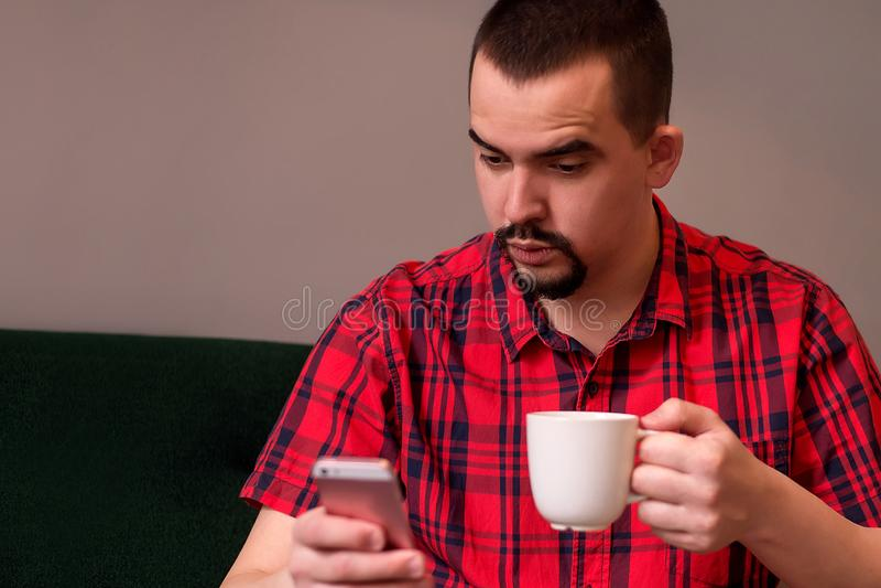 Den medelåldersa mannen med den förvånade framsidan som sitter på den gröna soffan med, rånar av kaffe och läsning eller att håll arkivbilder