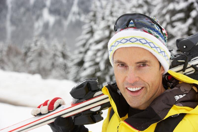 Den medelåldriga mannen skidar på ferie i berg fotografering för bildbyråer