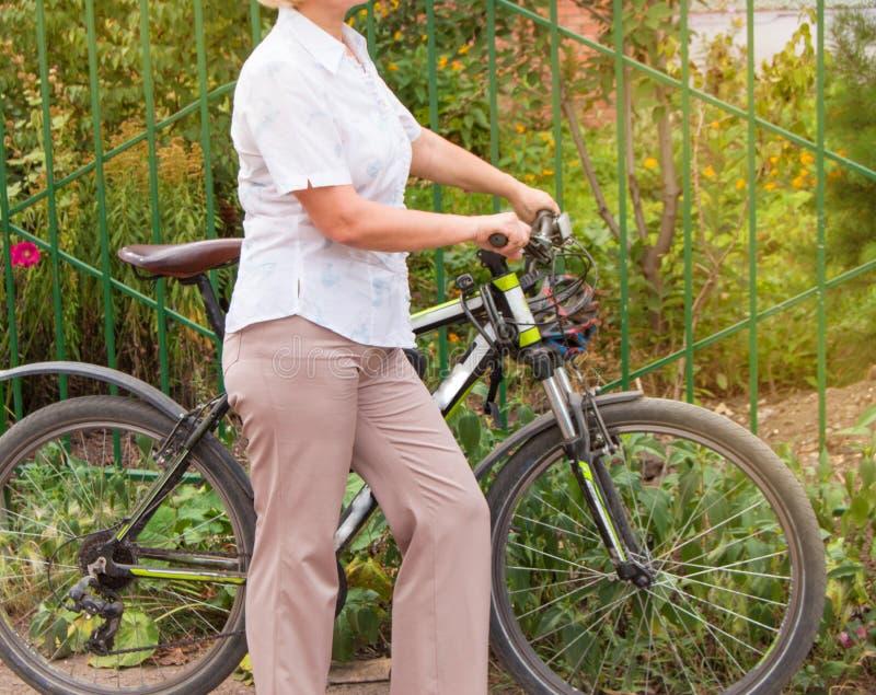 Den medel?ldersa attraktiva slanka kvinnan i ljus byxa och skjortast?llningar n?ra cykeln i parkerar p? en solig sommardag som cy royaltyfri bild
