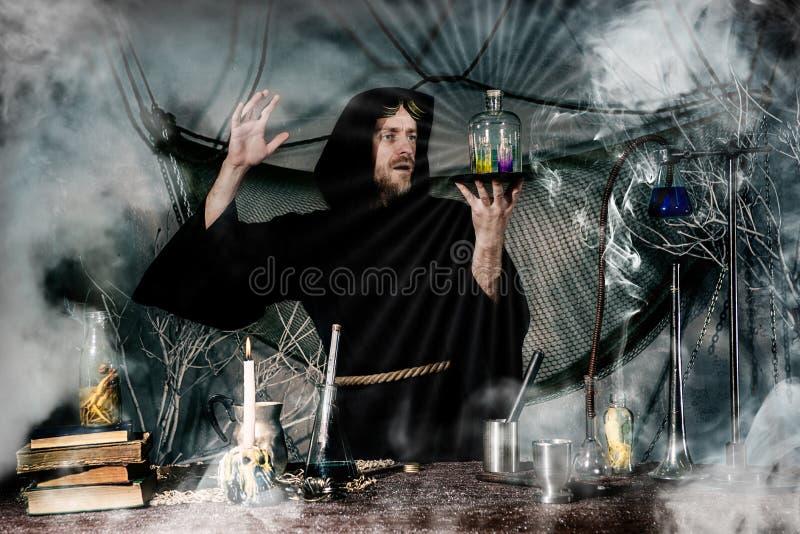 Den medeltida alkemisten att göra magisk ritual på tabellen i hans röklaboratorium royaltyfria foton