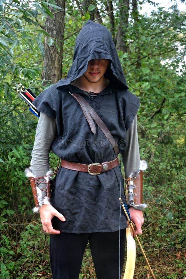 Den medeltida bågskytten med den svarta huven och färgade pilar i darrningen står med pilbågen arkivfoton