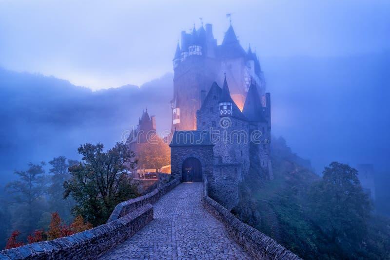 Den medeltida gotiska småstadEltz slotten i morgonmisten, Tyskland royaltyfri foto