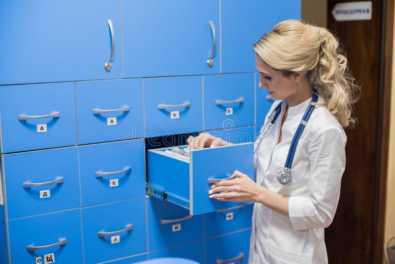 Den medicinska allmäntjänstgörande läkaren som söker för tålmodig ` s, antecknar i regeringsställning Kartotek arkivbild