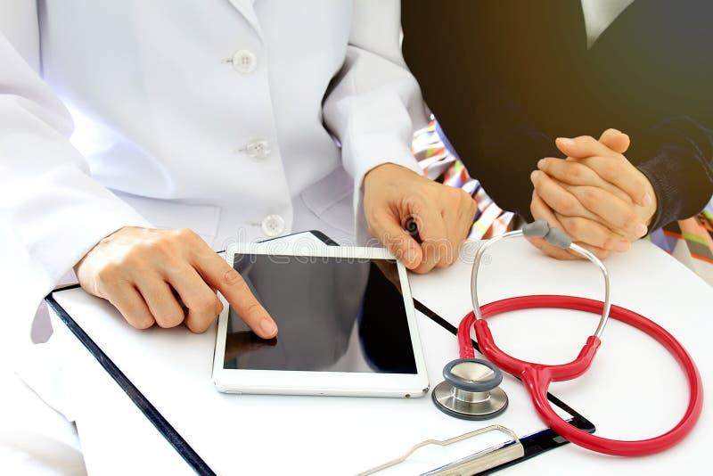 Den medicinska doktorn diskuterar med patienten om de vård- undersökningsresultaten, genom att använda minnestavladatoren arkivfoton