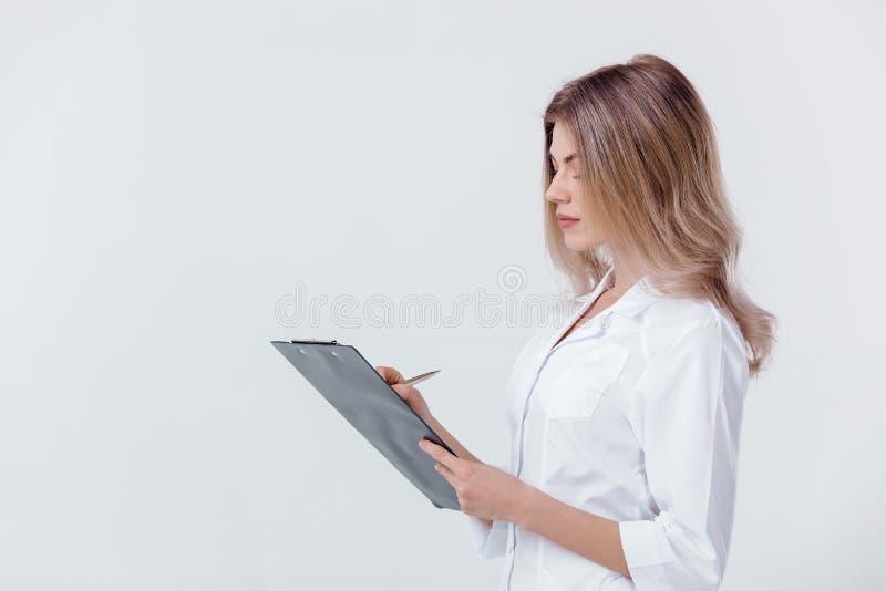 Den medicinska läkaredoktorskvinnan i det vita laget rymmer mappen med dokument på ljus bakgrund royaltyfria bilder