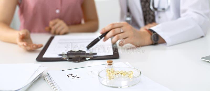 Den medicinska receptformen, kapslar och preventivpillerar ligger mot bakgrunden av en doktor och en patient som diskuterar hälsa royaltyfria foton
