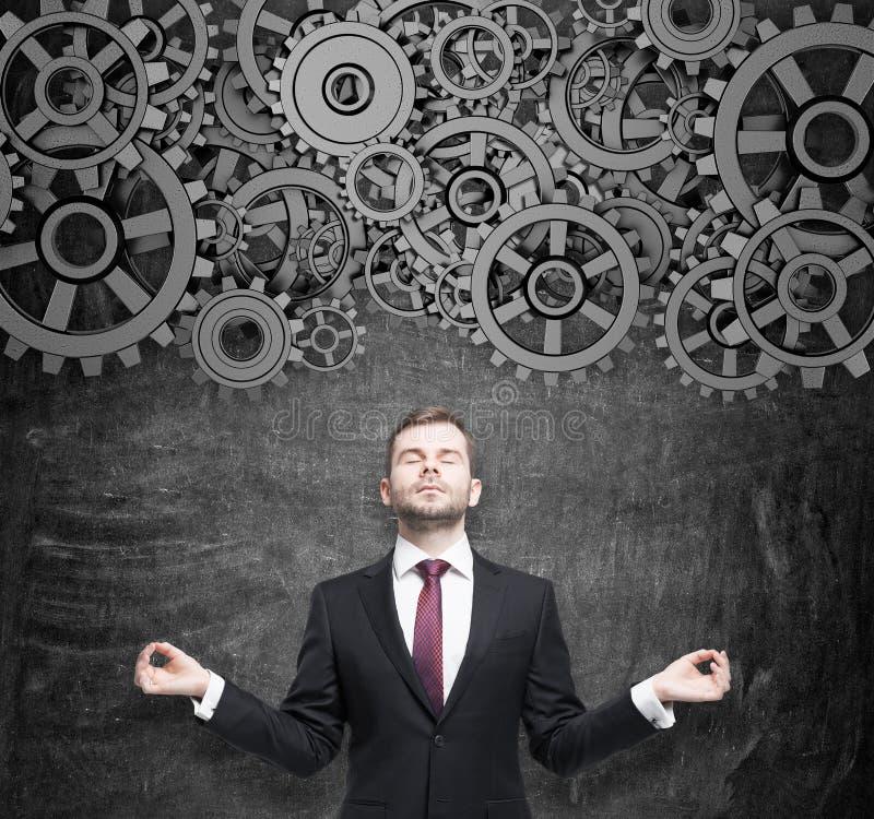 Den meditativa affärsmannen tänker om projektoptimisationen Kugghjul som ett begrepp av tankearbeteprocessen royaltyfria bilder