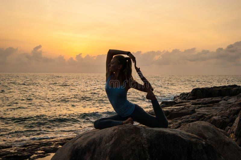 Den meditera flickan på en sten royaltyfri foto