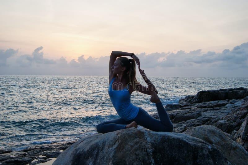Den meditera flickan på en sten arkivfoto