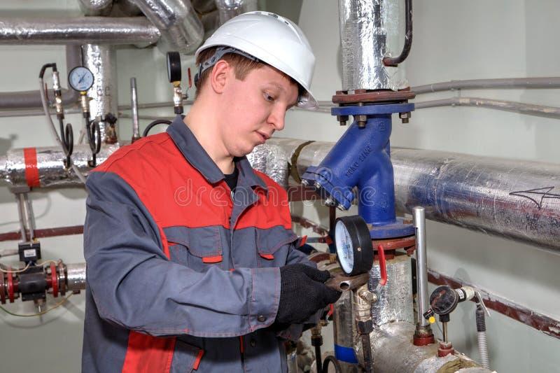 Den mekaniska teknikern ställer in manometern på röruppvärmningsystem arkivfoton