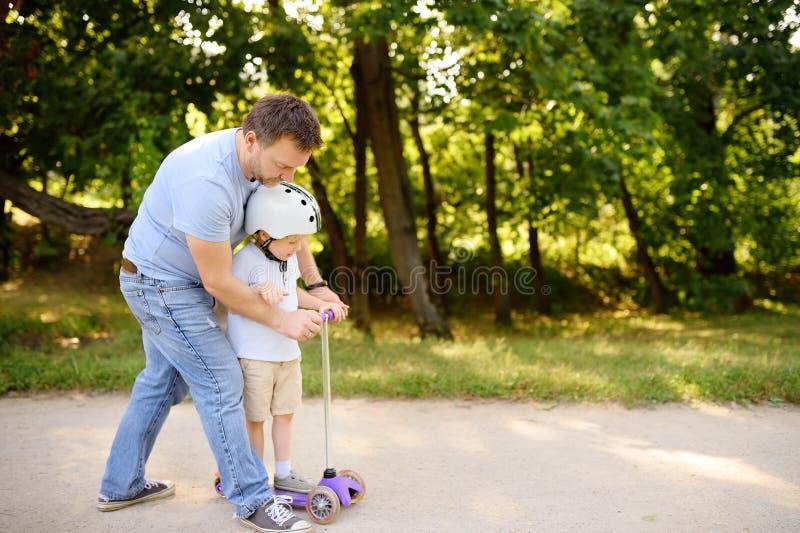 Den mellersta ålderfadern som visar hans litet barnson hur man rider en sparkcykel i sommar, parkerar arkivfoton