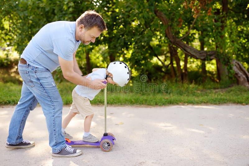 Den mellersta ålderfadern som visar hans litet barnson hur man rider en sparkcykel i sommar, parkerar royaltyfria bilder
