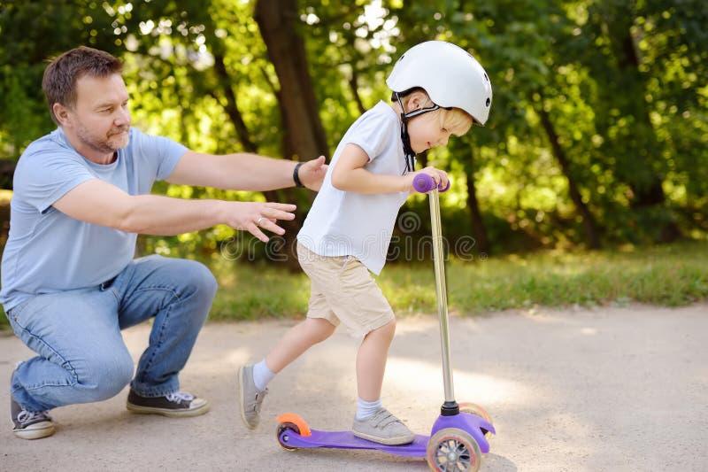 Den mellersta ålderfadern som visar hans litet barnson hur man rider en sparkcykel i sommar, parkerar royaltyfri bild