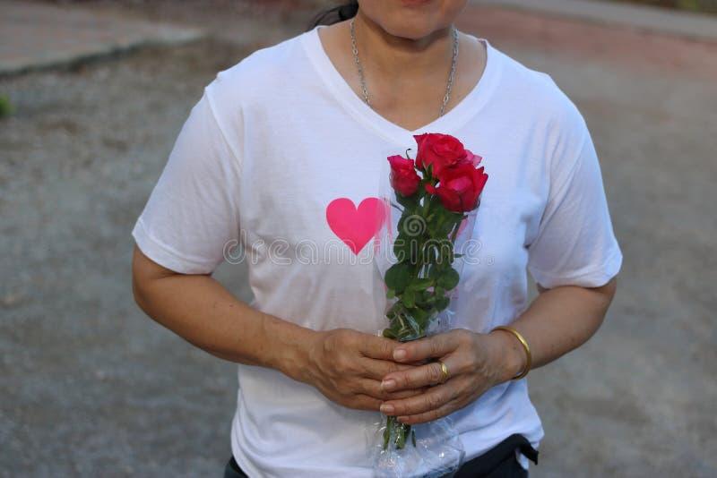 Den mellersta åldriga asiatiska kvinnan rymmer en härlig bukett av röda rosor Begrepp för dag för förälskelse- och romansvalentin royaltyfri fotografi