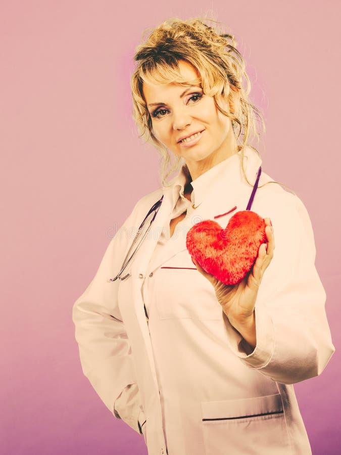 Den mellersta åldriga blonda doktorn tycker om hennes arbete arkivfoton