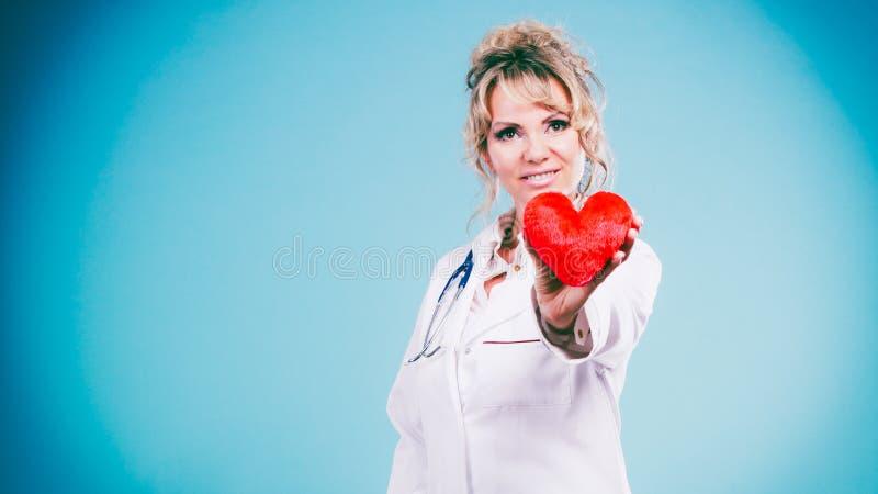 Den mellersta åldriga blonda doktorn tycker om hennes arbete royaltyfri bild