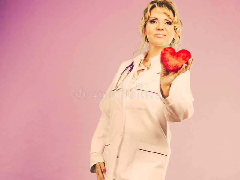 Den mellersta åldriga blonda doktorn tycker om hennes arbete royaltyfria bilder