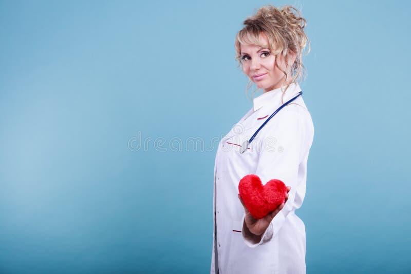 Den mellersta åldriga blonda doktorn tycker om hennes arbete fotografering för bildbyråer