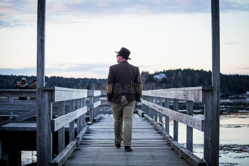 Den mellersta åldriga caucasian mannen som går på en pir som bär en blazer och en bästa hatt, sköt bakifrån royaltyfri fotografi