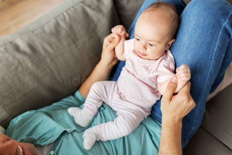 Den mellersta åldriga fadern med behandla som ett barn att ligga på soffan hemma royaltyfria bilder