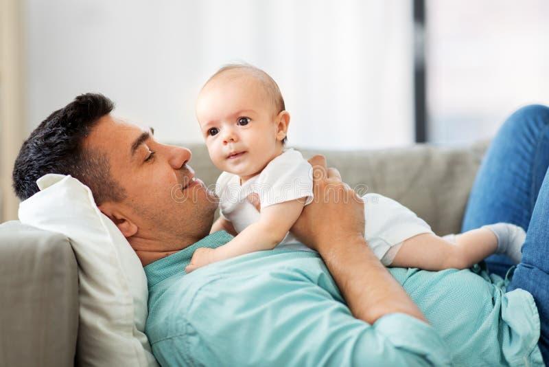 Den mellersta åldriga fadern med behandla som ett barn att ligga på soffan hemma arkivfoto