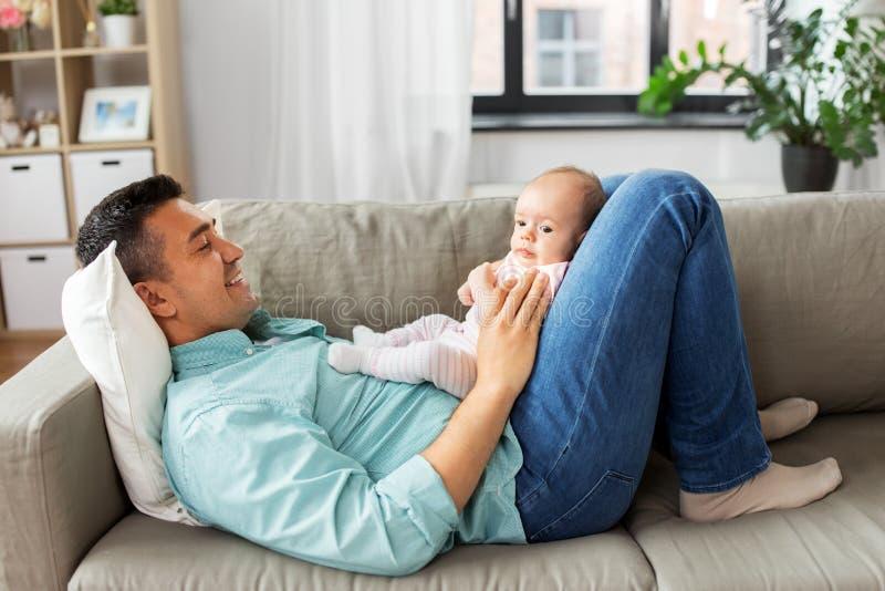 Den mellersta åldriga fadern med behandla som ett barn att ligga på soffan hemma arkivfoton