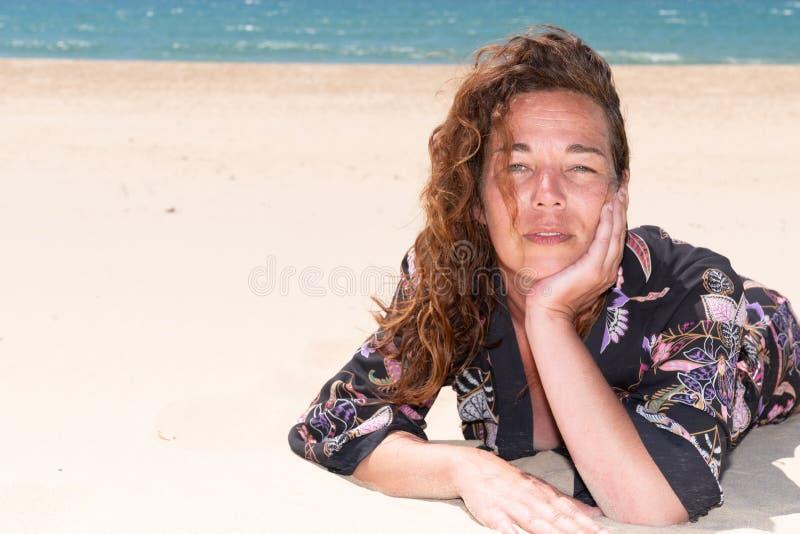 Den mellersta åldriga kvinnan tycker om semester av havet som ligger på sandstranden arkivfoton