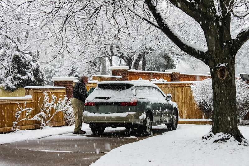 Den mellersta åldriga mannen med snö täckte bilen i körbana på extremt snöig dag med att falla för snö arkivfoton