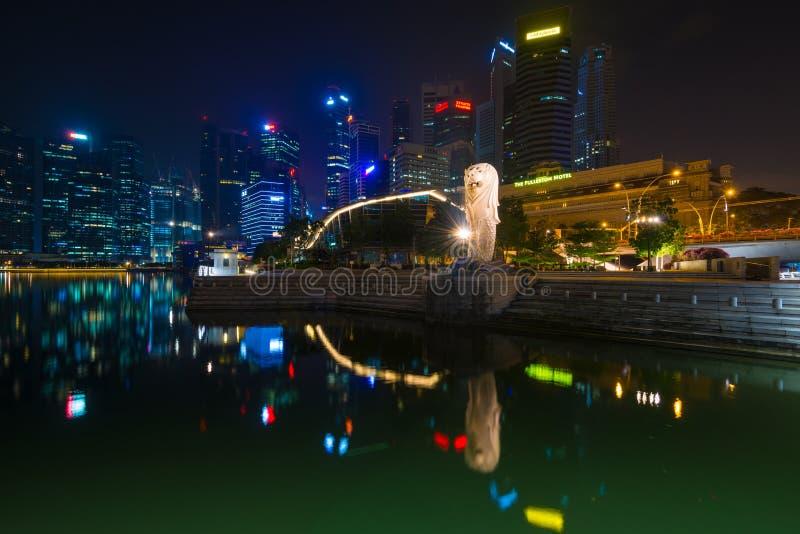 Den Merlion springbrunnen och den Singapore horisonten vid natt Merlion är arkivfoton