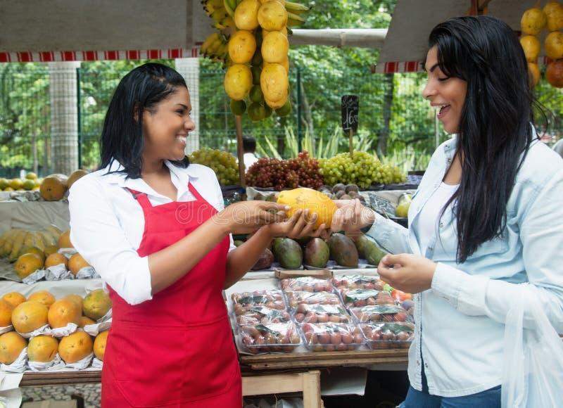 Den mexicanska försäljaren som talar med klienten på bönder, marknadsför royaltyfri fotografi