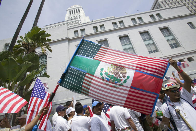 Den mexicanska flaggan läggas över över amerikanska flaggan framme av stadshuset, Los Angeles, medan hundratusentals invandrare s arkivbild