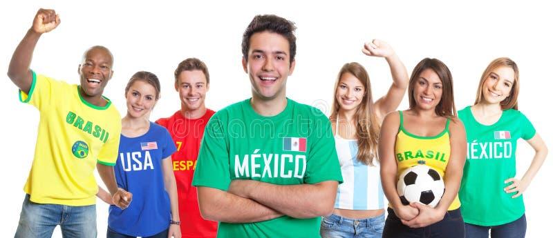Den mexicanska fotbollsfan med korsade armar och annan fläktar royaltyfria foton