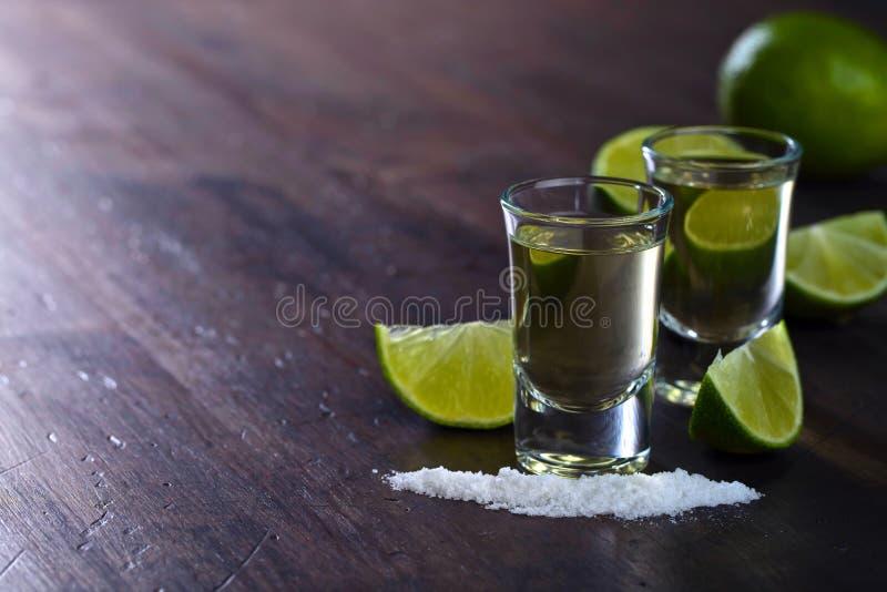 Den mexicanska guld- tequilaen med limefrukt och saltar arkivbilder