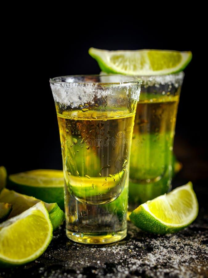 Den mexicanska guld- tequilaen med limefrukt och saltar på den svarta tabellen fotografering för bildbyråer