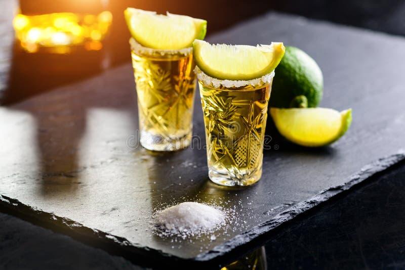 Den mexicanska guld- tequilaen med limefrukt och saltar på stenstångräknare royaltyfri bild
