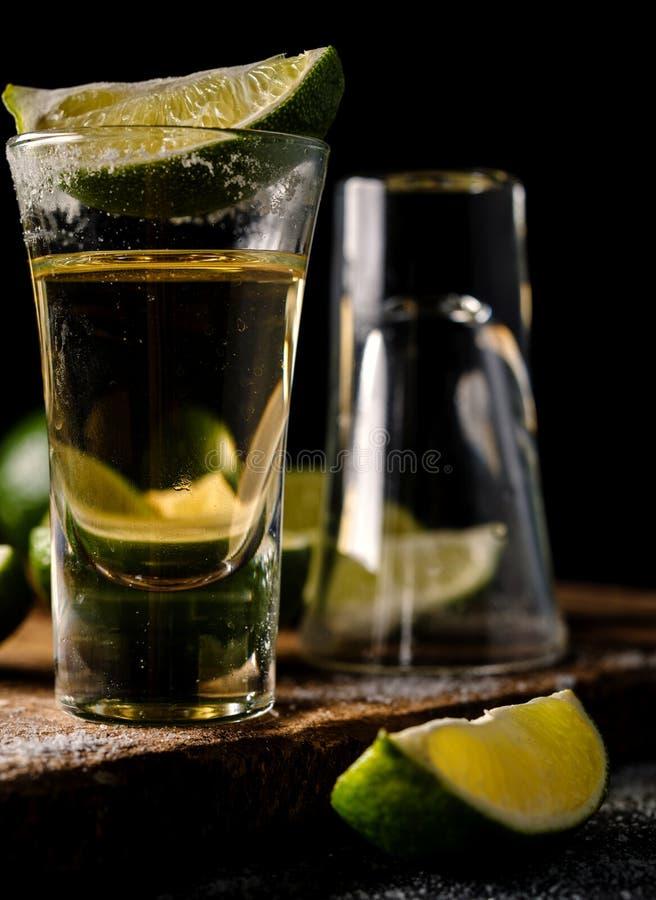 Den mexicanska guld- tequilaen med limefrukt och saltar på trätabellen fotografering för bildbyråer