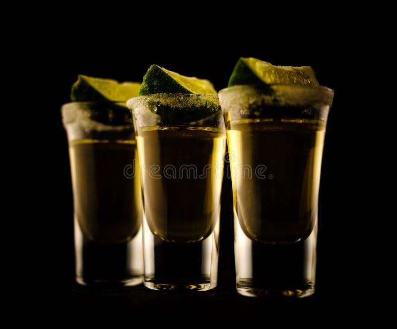 Den mexicanska guld- tequilaen med limefrukt och saltar på trätabellen royaltyfri fotografi
