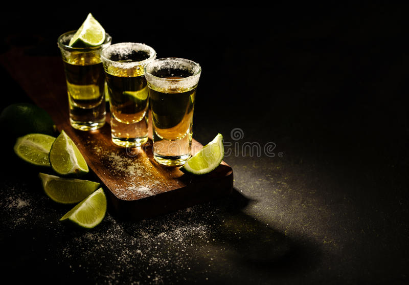 Den mexicanska guld- tequilaen med limefrukt och saltar på trätabellen arkivfoton