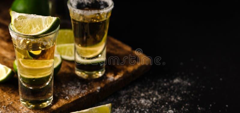Den mexicanska guld- tequilaen med limefrukt och saltar på trätabellen arkivbild