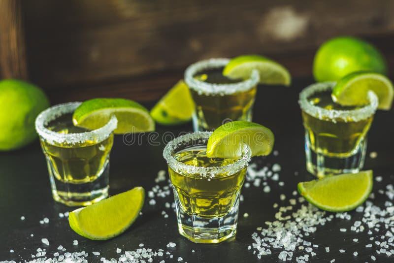 Den mexicanska guld- tequilaen som skjutas med limefrukt och, saltar på svart stenar tabellyttersida arkivfoto