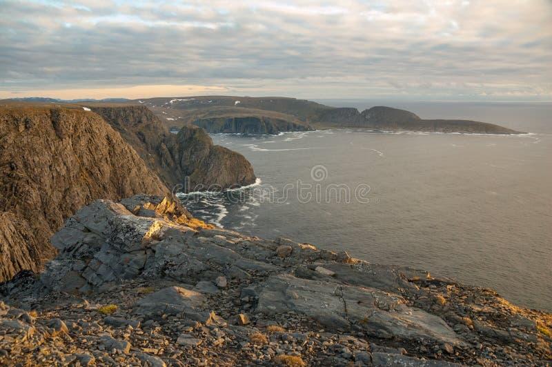 Den midnatta solen nära Nordkapp exponerar nord-fasadbeklädnad klippor på 1a arkivbilder