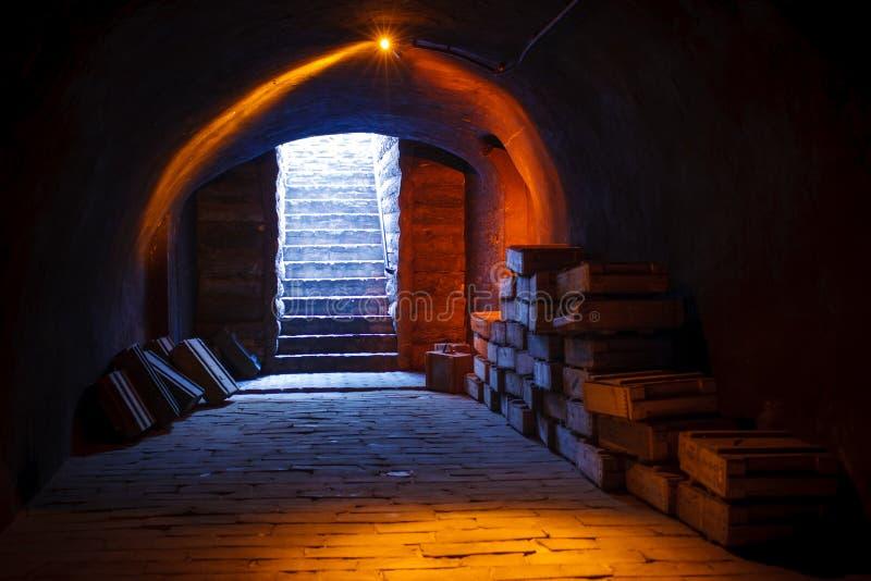Den militära källaren uppför trappan avbildar från en militär källare med buntar av gamla militära ammunitionaskar och uppför tra arkivfoto
