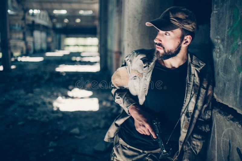 Den militära mannen är stå och luta till betongväggen Han ser till det vänstert Grabben rymmer det svarta vapnet i assistent arkivbild
